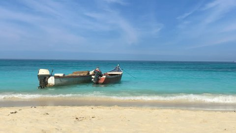 Picturesque empty beach with two boats in Playa Blanca, Cartagena, Colombia.