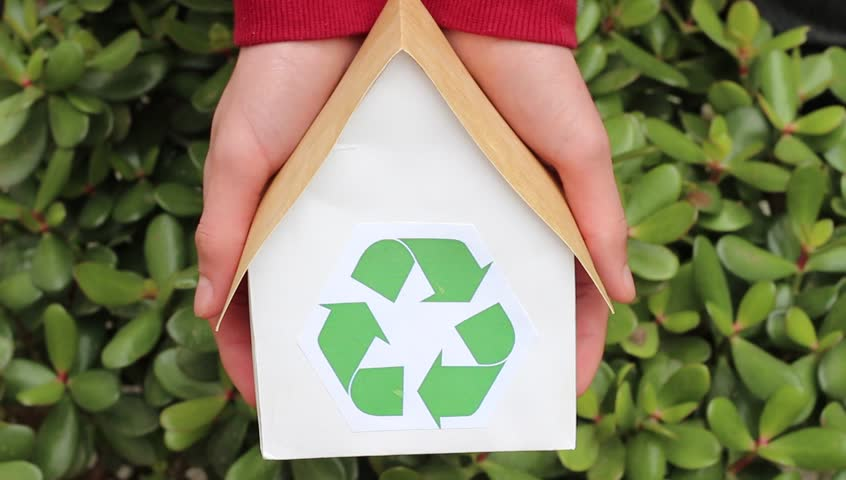 Hands Holding House With Green Recycling Sign. People, ecology, environment and conservation concept. Close up of hands holding house with green recycling symbol