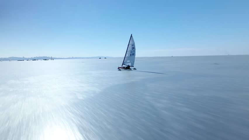 Sailing ship yacht skates on ice skate. Ice-boat sailing. Sport event competition on cold ice Russia North Asia Baikal. Winter frozen sunny snow day. Aeria together with. Drone high speed