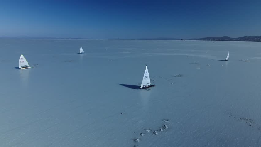 Sailing ships skates on ice skate. Ice-boat sailing. Interesting unusual Unique Sport event competition on cold ice Russia Asia North Baikal. Winter frozen sunny snow day. Aerial above. High altitude