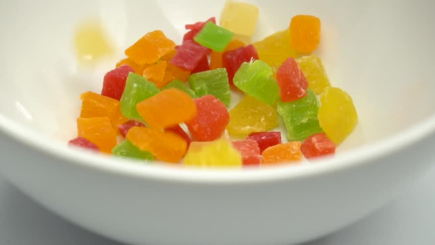 Colorful cubes candied fruit kiwi, mango, pineapple, strawberry (gummy candy) are falling. Slow motion