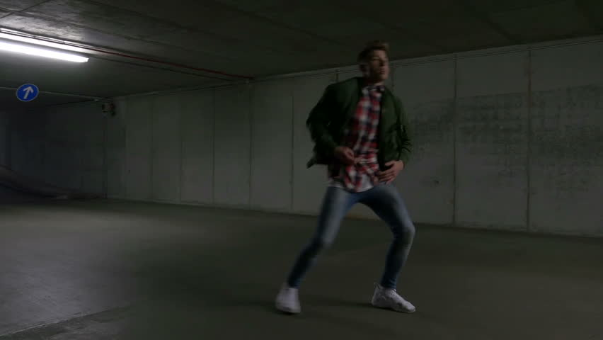 A young male dancer gracefully dances in an underground parking lot. Full body shot. | Shutterstock HD Video #1008456319