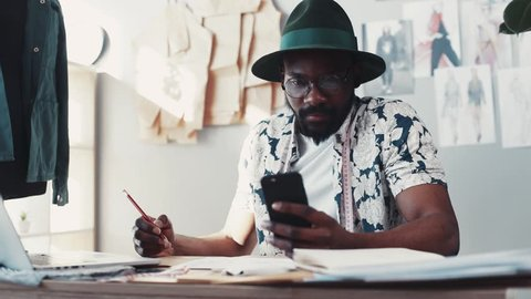 Young fashion blogger surfs the Internet via his smartphone, and sketches out his new collection in his cozy office. Trendy outfit, hipster look. Male portrait, slow motion