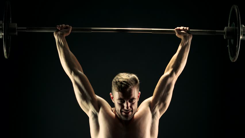 Young sportsman lifting heavy barbell. Hard training of professional sportsman, dark background. Power, strength and persistence. | Shutterstock HD Video #1008478939
