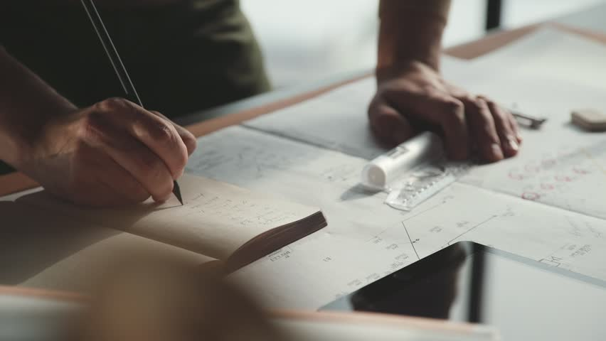 Architect's desk: drawings, tape measure, ruler and other drawing tools. Engineer works with drawings in a bright office, close-up. Insturments and office for designer. Male hands draw with a pencil.