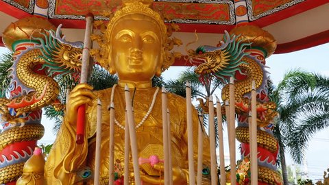 Golden Buddha statue in the Chinese temple. Thailand. Fragrant sticks smoke and smolder nearby. Temple in Chinese style, with many Chinese ornaments, Fontan, gold statue, dragons, statuettes, and