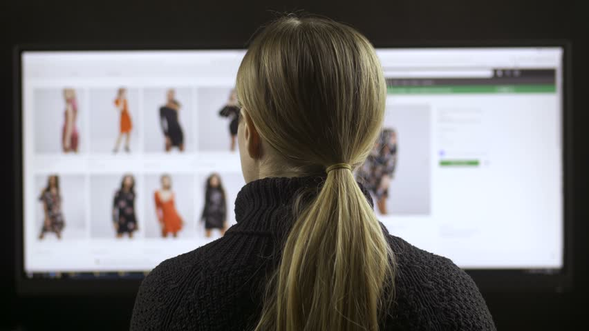 Back view of female sitting at wide screen computer and fashion shopping online. Woman searching clothing apparel on the internet, browsing webpages and looking for discounts during sale | Shutterstock HD Video #1008495079