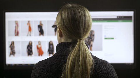 Back view of female sitting at wide screen computer and fashion shopping online. Woman searching clothing apparel on the internet, browsing webpages and looking for discounts during sale