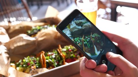 Food photo with a mobile phone a guy in Mexican cuisine restaurant takes pictures for social media