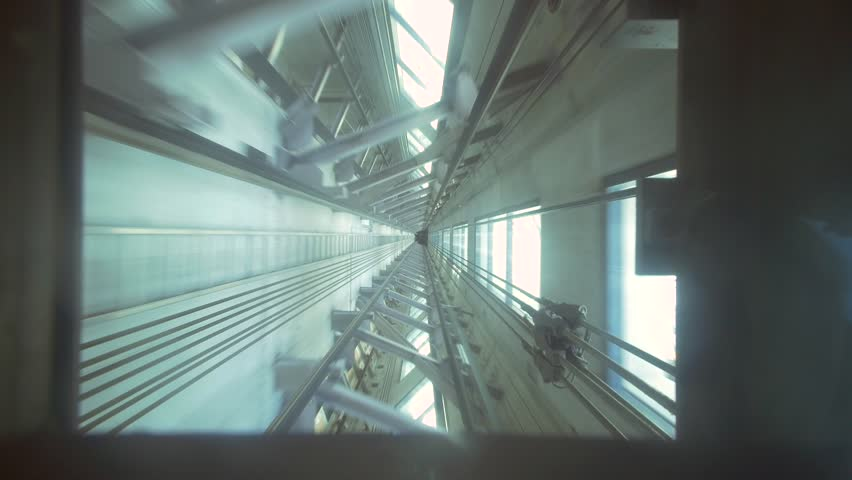 Shot through the bottom of a glass elevator whilst the elevator is descending | Shutterstock HD Video #1008522259