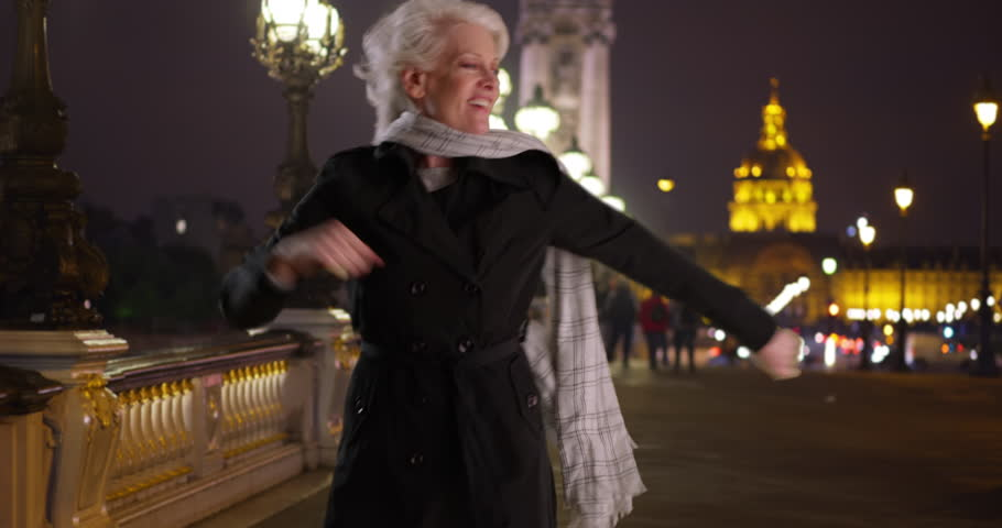 Carefree energetic mature woman dancing on the Alexandre III bridge in Paris at night. Joyful active senior dances and spins around with scarf on cold fall evening in France. 4k | Shutterstock HD Video #1008530359