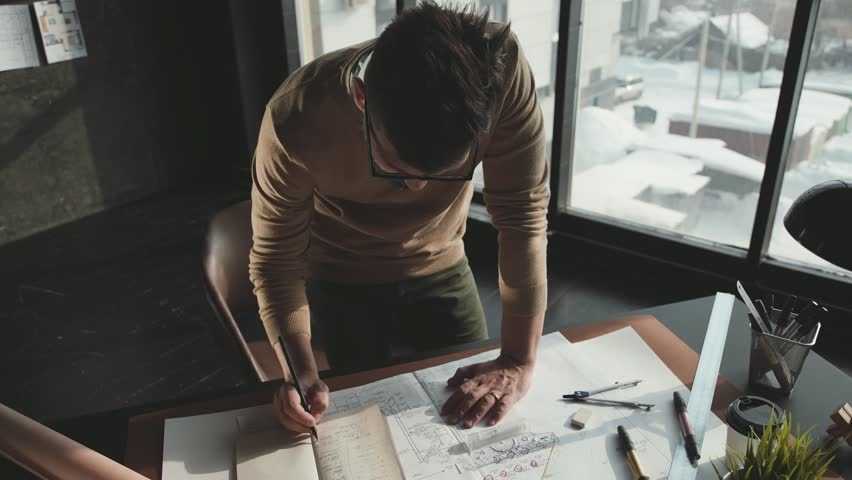 Hipster engineer works with blueprint. Shoot from above. Young architectural engineer working in office. Bearded man in glasses makes sketches. Loft style, minimalistic interior, drawings on the table
