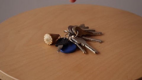 Taking Keys to little table and Taking them from table. Arriving / Leaving Home concept.Slow motion.