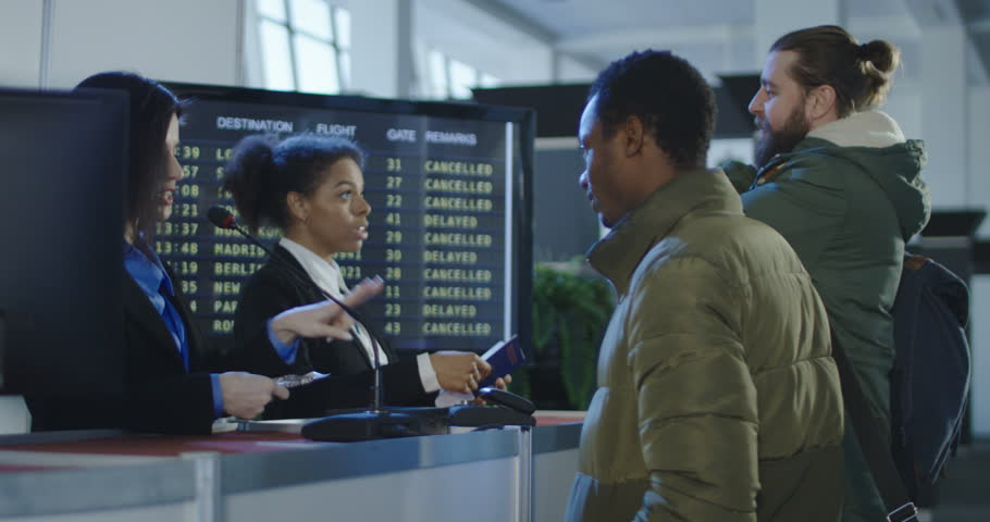 Smiling female security agent at an airport working at the check-in desk for boarding a flight handing back a passport and ticket or boarding pass to a male passenger.
