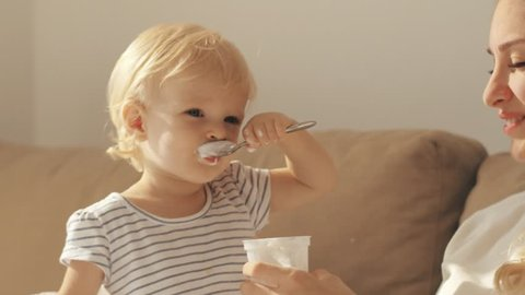 Funny child eating yogurt sitting on couch beside young mother. Little girl learning to eat yogurt with spoon together happy mother