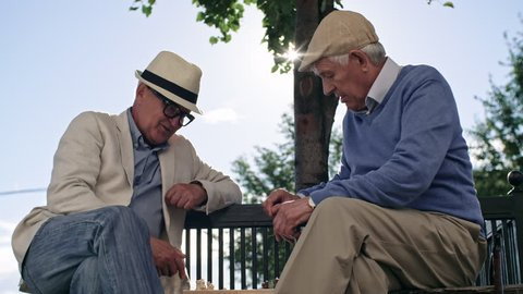 Two senior male friends sitting opposite each other on bench in park, talking and playing chess