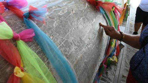 Thai people write use powder rubbing on surface of hopea odorata or Ta-khian finding and plead for lucky number at Wat Chedi or Ai Kai Wat Chedi at Sichon in Nakhon Si Thammarat, Thailand