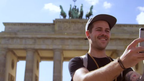 guy takes a selfie with the Brandenburg gate in the back