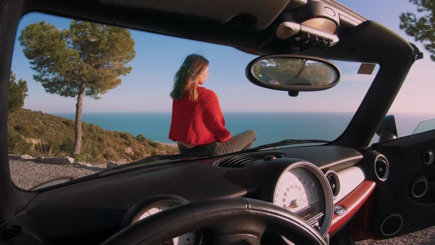 Cinemagraph from inside car of drivers seat of young beautiful woman or model sit on hood of convertible cabriolet car and overlook ocean views. Concept influencer or blogger travel lifestyle | Shutterstock HD Video #1008626719