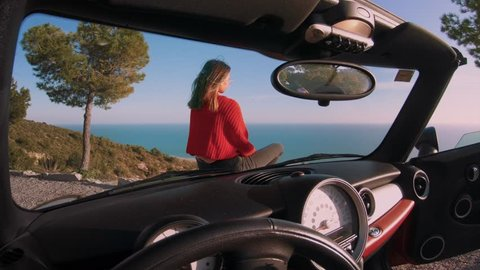 Cinemagraph from inside car of drivers seat of young beautiful woman or model sit on hood of convertible cabriolet car and overlook ocean views. Concept influencer or blogger travel lifestyle