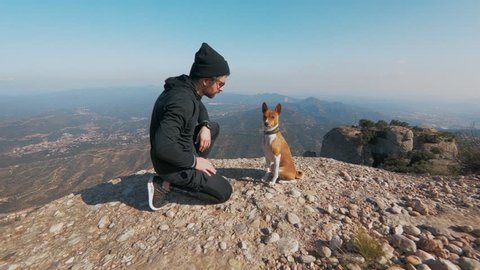 Steadycam shot of adorable cute puppy dog of basenji breed give high-five to owner of pet, active sporty man in athletic outfit during hike or adventure trip through epic mountains or park