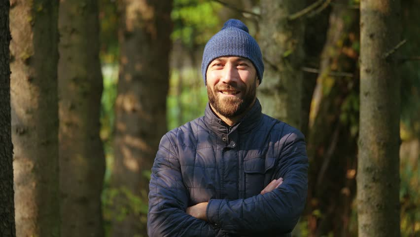 Portrait Happy smiling and laughing bearded guy crossing his arms looking at camera. outerwear and knitted hat. nature background. slow motion #1008628069