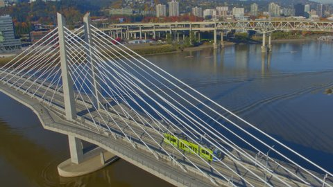 An aerial view of the Tilikum Crossing Bridge in Portland Oregon over the Willamette River on a sunny morning with a colorful trolley and still waters ripple from a boat and downtown Portland in the b