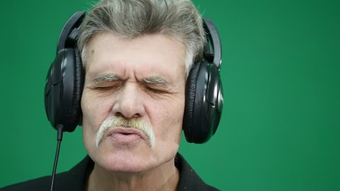 The old man in headphones, listening to music, dancing, smiling, cheerful