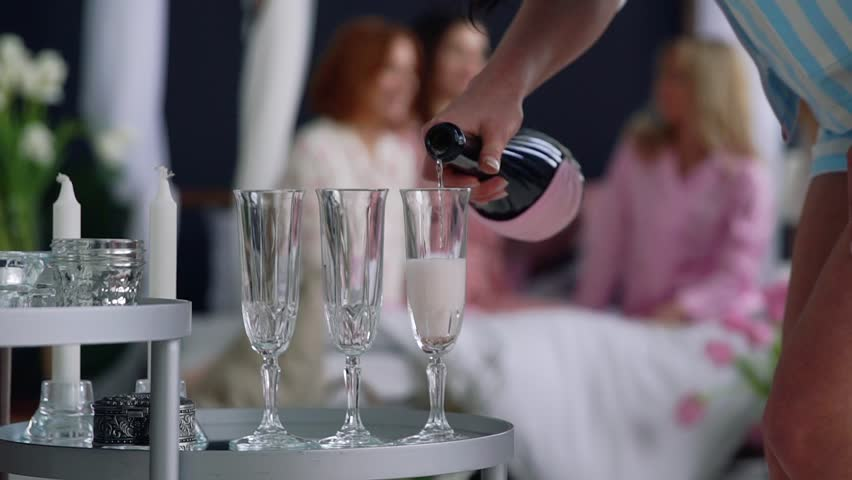 Close-up of a beautiful girl fills with champagne glasses for girlfriends who have fun in the background at a bachelorette party.
