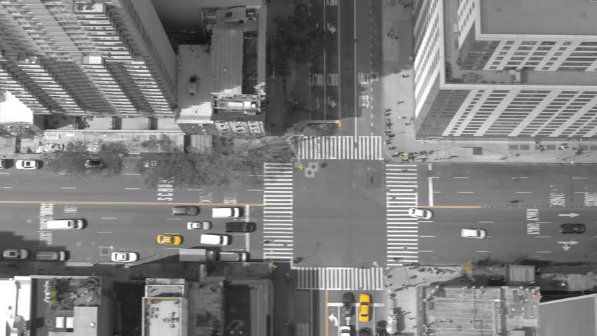 AERIAL TOP DOWN, ISOLATED YELLOW: Tall urban buildings surround busy metropolis city avenue filled with traffic and pedestrians. Flying over busy intersections and skyscrapers in downtown New York. | Shutterstock HD Video #1008671659
