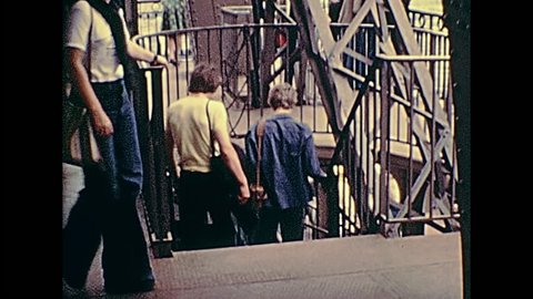 PARIS, FRANCE - CIRCA 1976: Tourists in 70s dress, descending from the observation deck of Paris from Eiffel Tower. Historic archival footage in Paris city of France in 1970s.