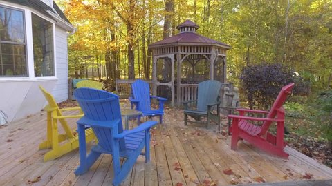 adirondack and muskoka chairs on deck with fall colours 4k gimbal approach real estate
