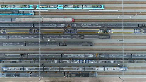 Aerial top down footage of railway transportation hub showing the different trains parked next to each other on the rails very smooth and right movement keeping the horizontal lines straight 4k