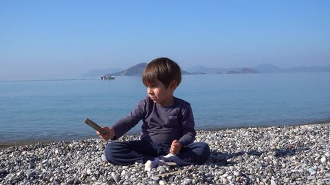 4K Boy catapults stones at the beach, a boat passing by in the background