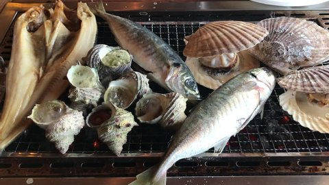 Various kind of grilled sea shells scallop(Hotate), horned turban sea snail (Sazae) and fish at Wakayama fish market, Japan.Roasted fish on the hot grill with smoke.