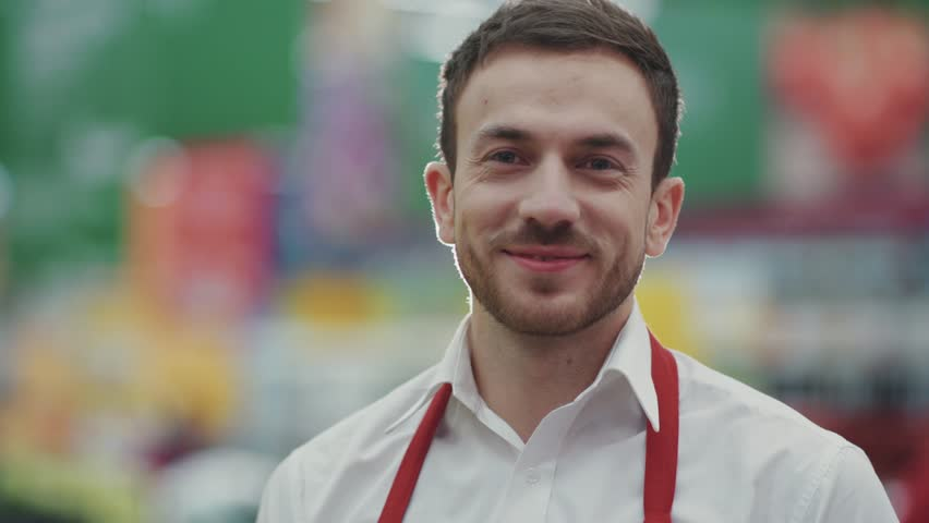 Happy face seller man in supermarket look camera smile vegetable business beautiful fresh produce retail shop worker food choosing young grocery healthy mall model shopping product portrait close up