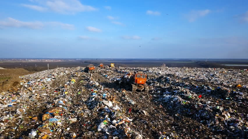 City Dump. The Bulldozer Compacts the Garbage on the Landfill. Wastes of Human Life. Aerial View