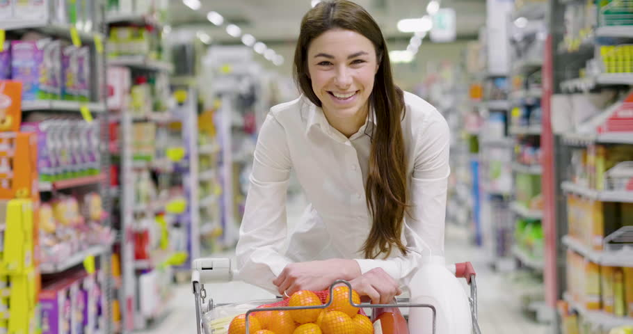 Portrait a beautiful woman, goes shopping for the house and buy products for eating, cleaning the house and products for the care of your body in a supermarket. Concept of: shopping, family and home. | Shutterstock HD Video #1008741689
