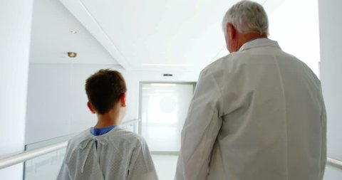 Rear view of doctor walking with patient in hospital corridor