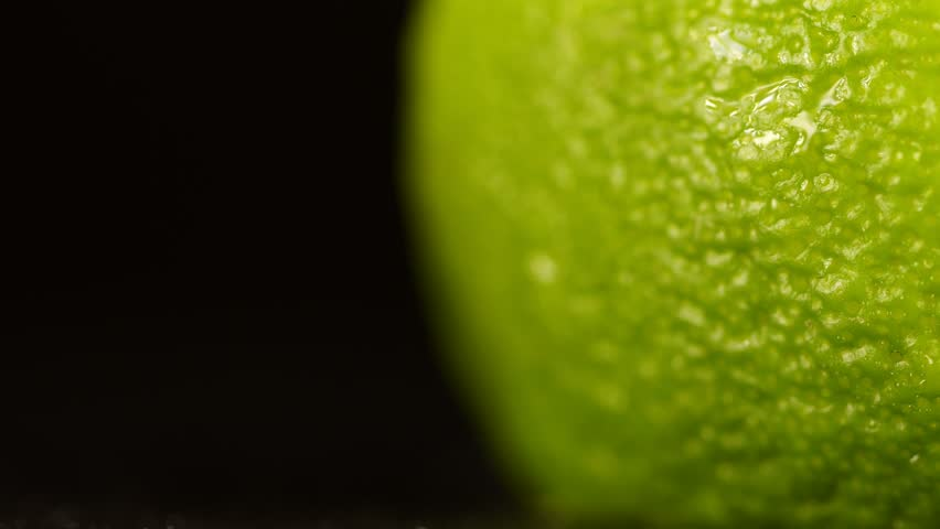 Lime crust close up on a black background. Limes with Water Drops. Macro shooting. Water drops on a citrus close up. Macro shooting of a citrus. Green juicy lime