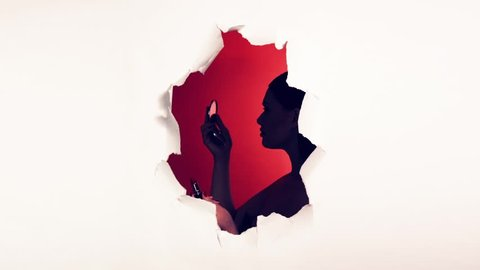Silhouette of girl in hole in white background. The girl makes up her lips. Peeping. Torn hole in white paper background. Place for text. Red background. Concept for advertising lipstick.