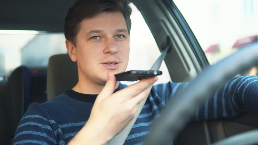 A young attractive man is using a mobile phone on the speakerphone in the car | Shutterstock HD Video #1008770249