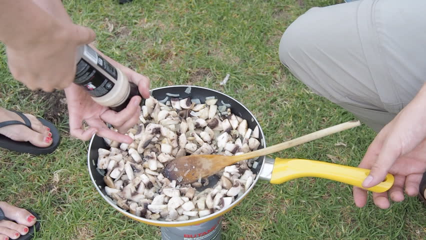 Sautéing onions and mushrooms in frying pan while camping