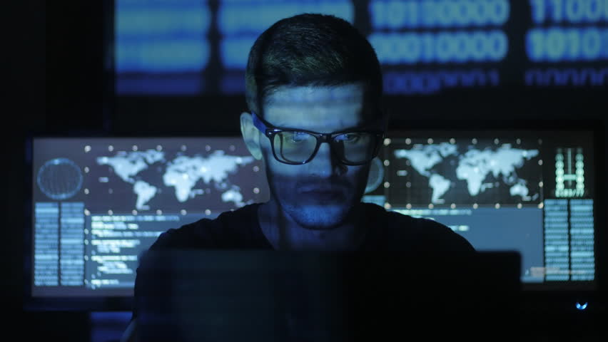 Hacker programmer in glasses is working on computer while blue binary code characters reflect on his face in cyber security center filled with display screens. | Shutterstock HD Video #1008776849