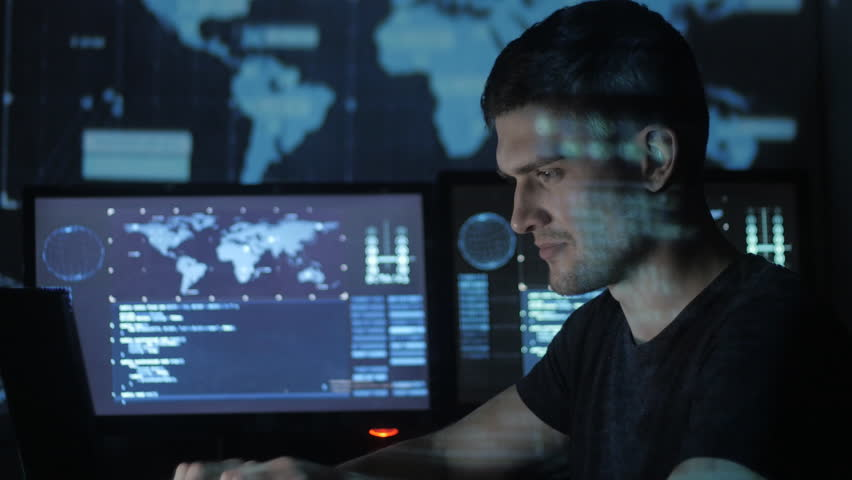 Male hacker programmer working at computer while blue code characters reflect on his face in cyber security center filled with display screens. | Shutterstock HD Video #1008780359