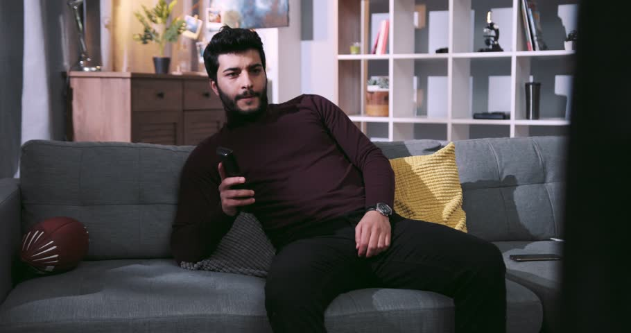 Handsome bearded man sits on a sofa, uses remote control, switches the channels, founds nothing interesting, goes away. Couch potato, having rest, weekend. Slow motion, camera stabilizer shot, male