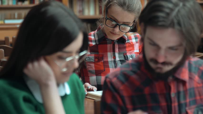 Students reading in library, smart bearded boy turning book pages, intelligent girl in glasses talking to him, concept of pairwork, closeup