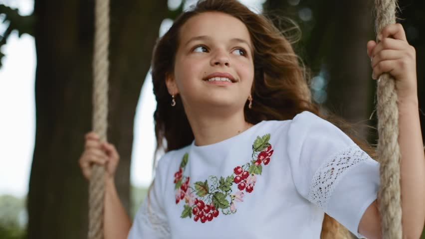 Cute smiling long-haired girl sways on a wooden swing seat in a garden. Dreamy mood, having fun, childhood memories. Strong wind playing with her hair. Slow motion