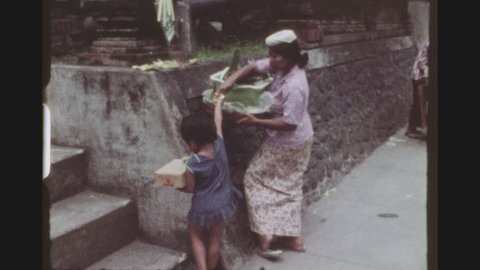 INDONESIA, BALI DENPASAR, FEBRUARY 1977. Three Shot Sequence Of Busy Gajah Mada Main Street, With A Mother And Two Children Carrying Shopping Baskets On Their Heads.