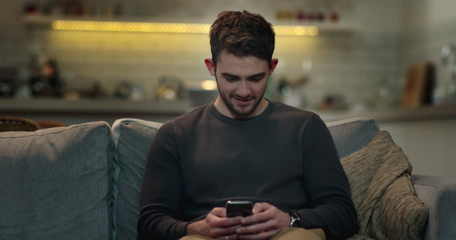 Smiley young man web surfing on his mobile phone on the sofa at home. | Shutterstock HD Video #1008851189